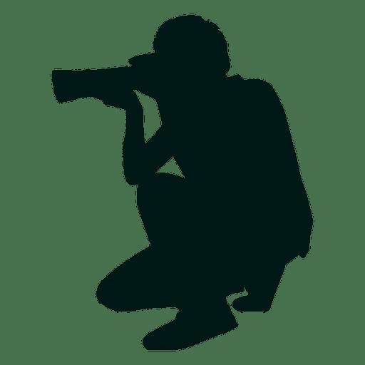 Fotógrafo arrodillado silueta