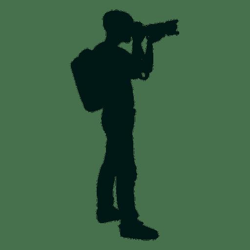 Fotógrafo con mochila disparando silueta