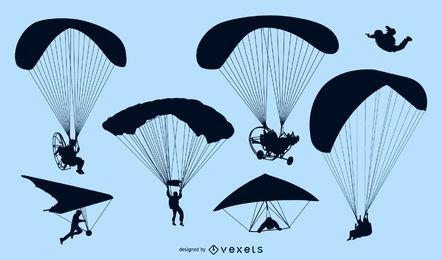 Conjunto de siluetas de paracaídas y paracaidistas.