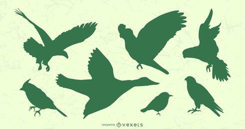 Conjunto de silhueta de pássaros voando