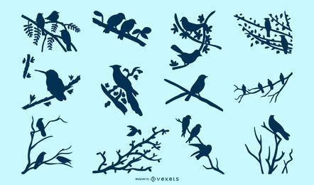 Paquete de silueta de pájaros en ramas de árboles
