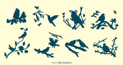 Conjunto de silhuetas de pássaros em galhos de árvores