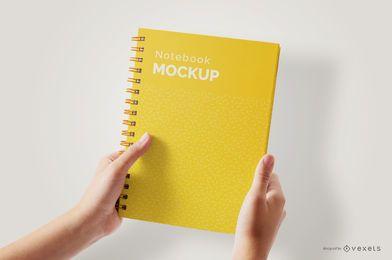 Manos sosteniendo maqueta de cuaderno