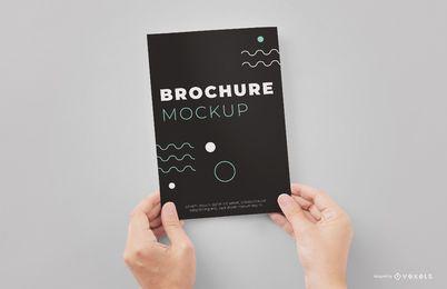 Mãos segurando brochura maquete