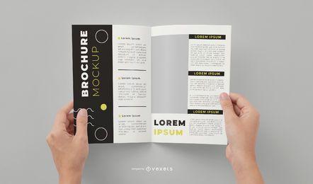 Maquete de mãos de brochura aberta