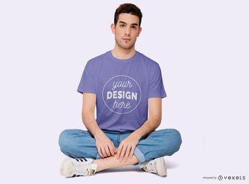 Rapaz sentado com pernas cruzadas t-shirt Maquete