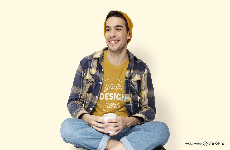 Hombre sujetando maqueta de camiseta taza