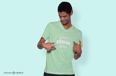 Modelo masculino apontando camiseta para maquete