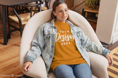 Mulher na cadeira maquete da camiseta da sala de estar
