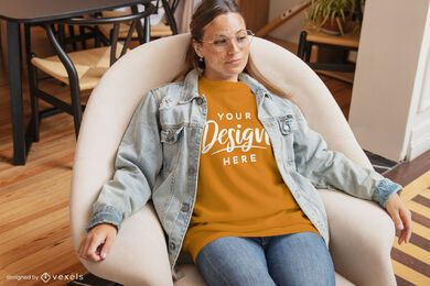 T-Shirt-Modell der Frau im Stuhlwohnzimmer