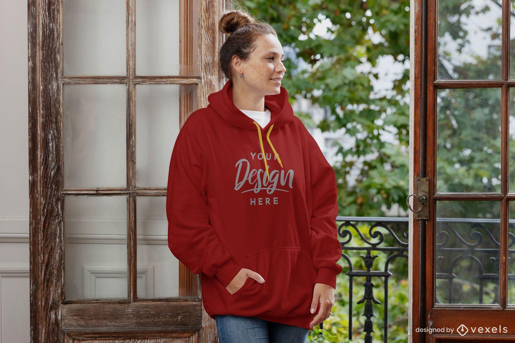 Woman against window hoodie mockup