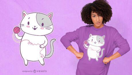 Gato fofo brincando com o desenho de uma camiseta de lã