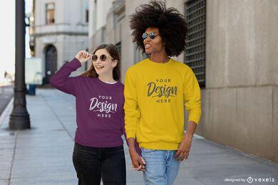 Glückliches Paar, das Händchen-Sweatshirt-Modell hält