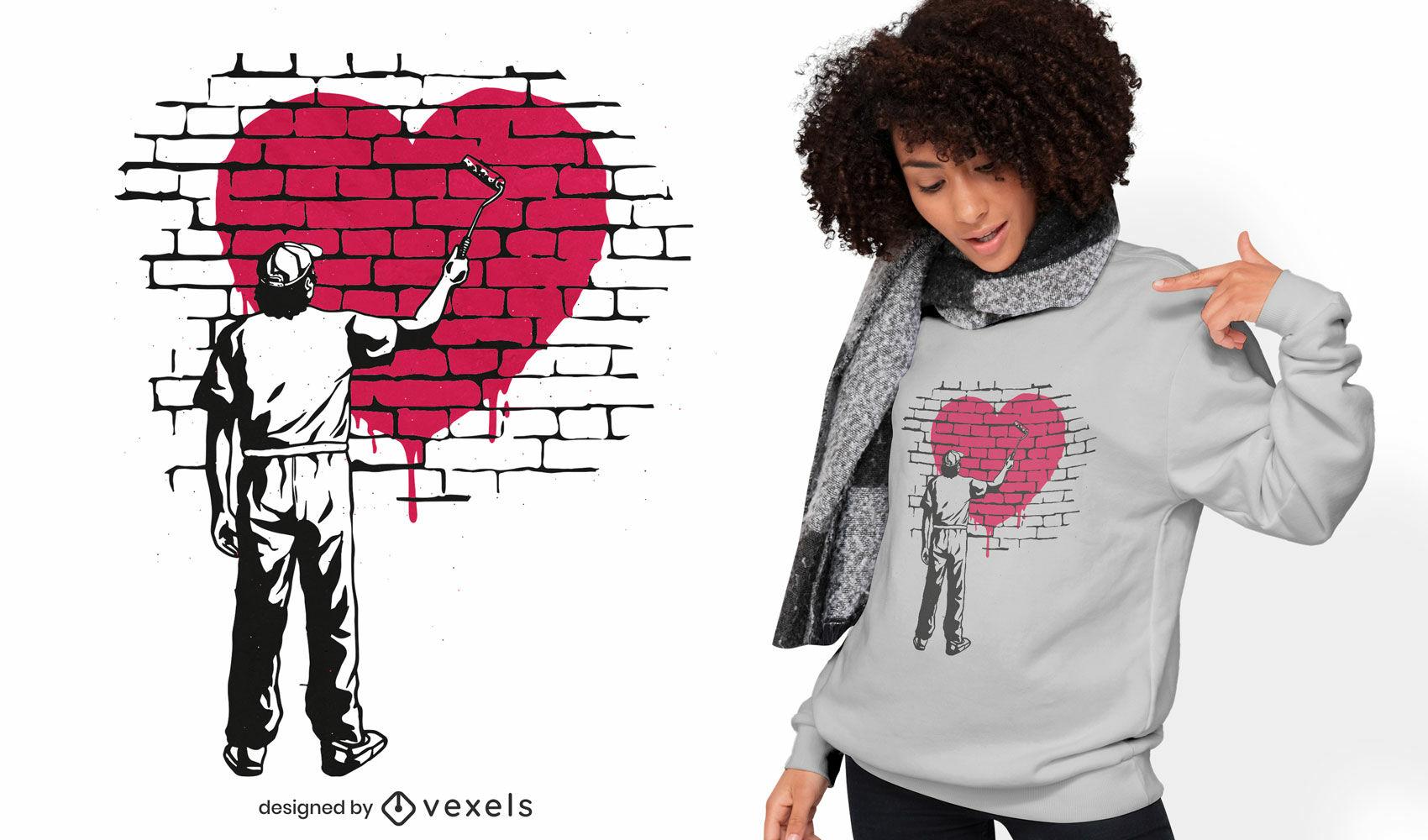 Homem pintando um coração no design de uma camiseta na parede