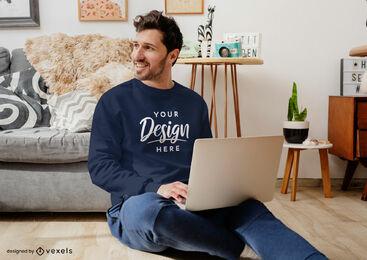 Man in living room with laptop sweatshirt mockup