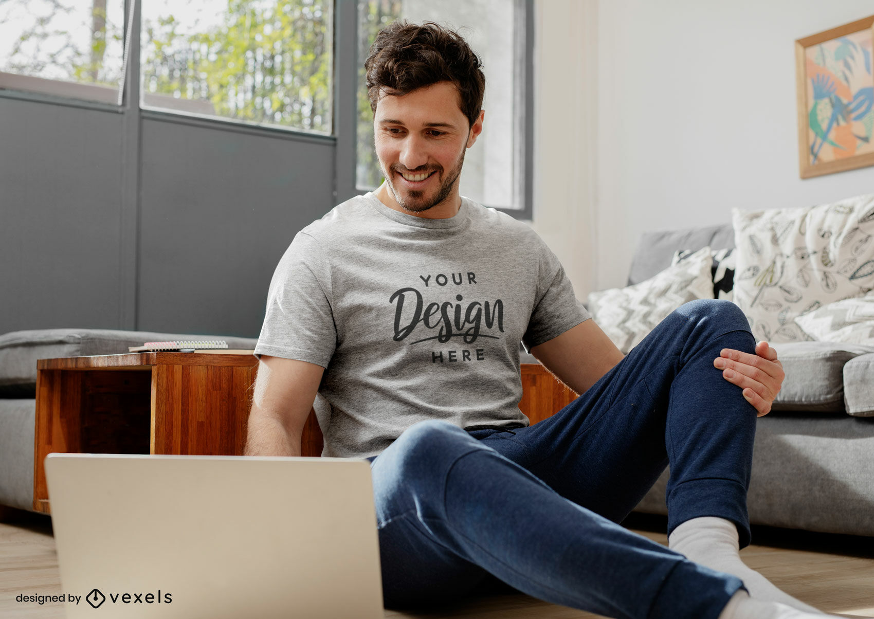 Hombre de maqueta de camiseta gris en sala de estar sentado