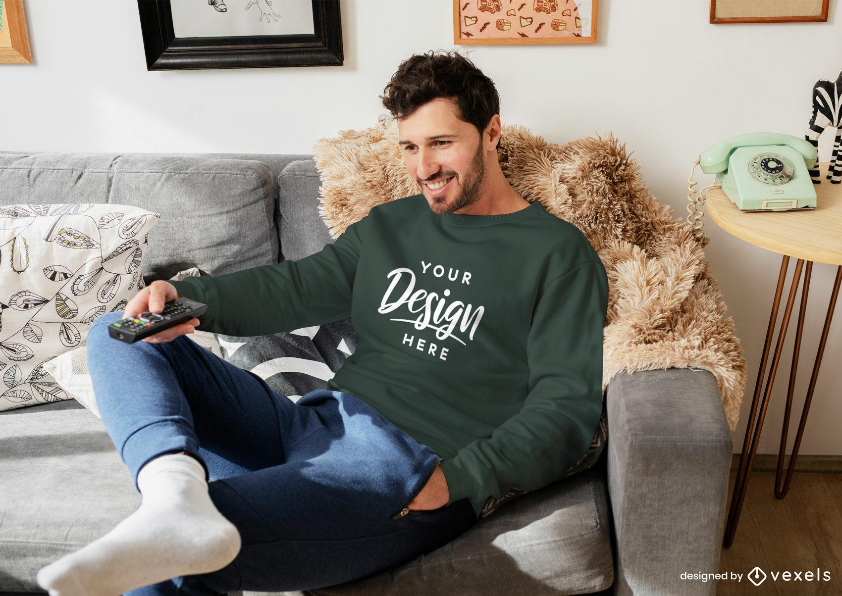 Hombre de maqueta de sudadera verde en la sala de estar sentado