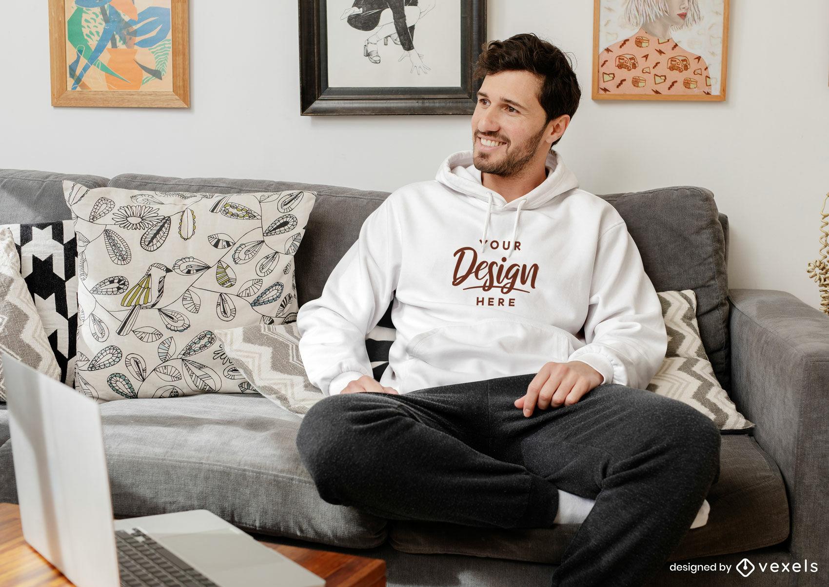Weißer Hoodie-Mockup-Mann, der im Wohnzimmer sitzt