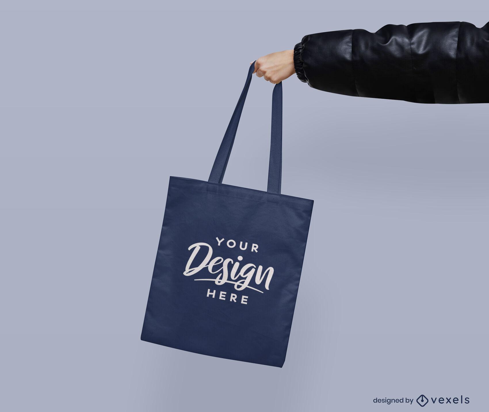 Hand, die flachen Hintergrund des blauen Einkaufstaschenmodells hält