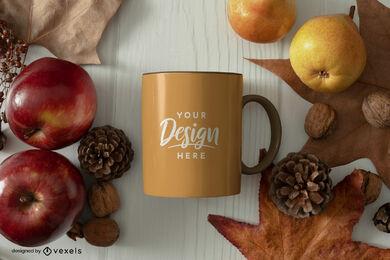 Maquete da caneca marrom com maçãs e folhas no outono