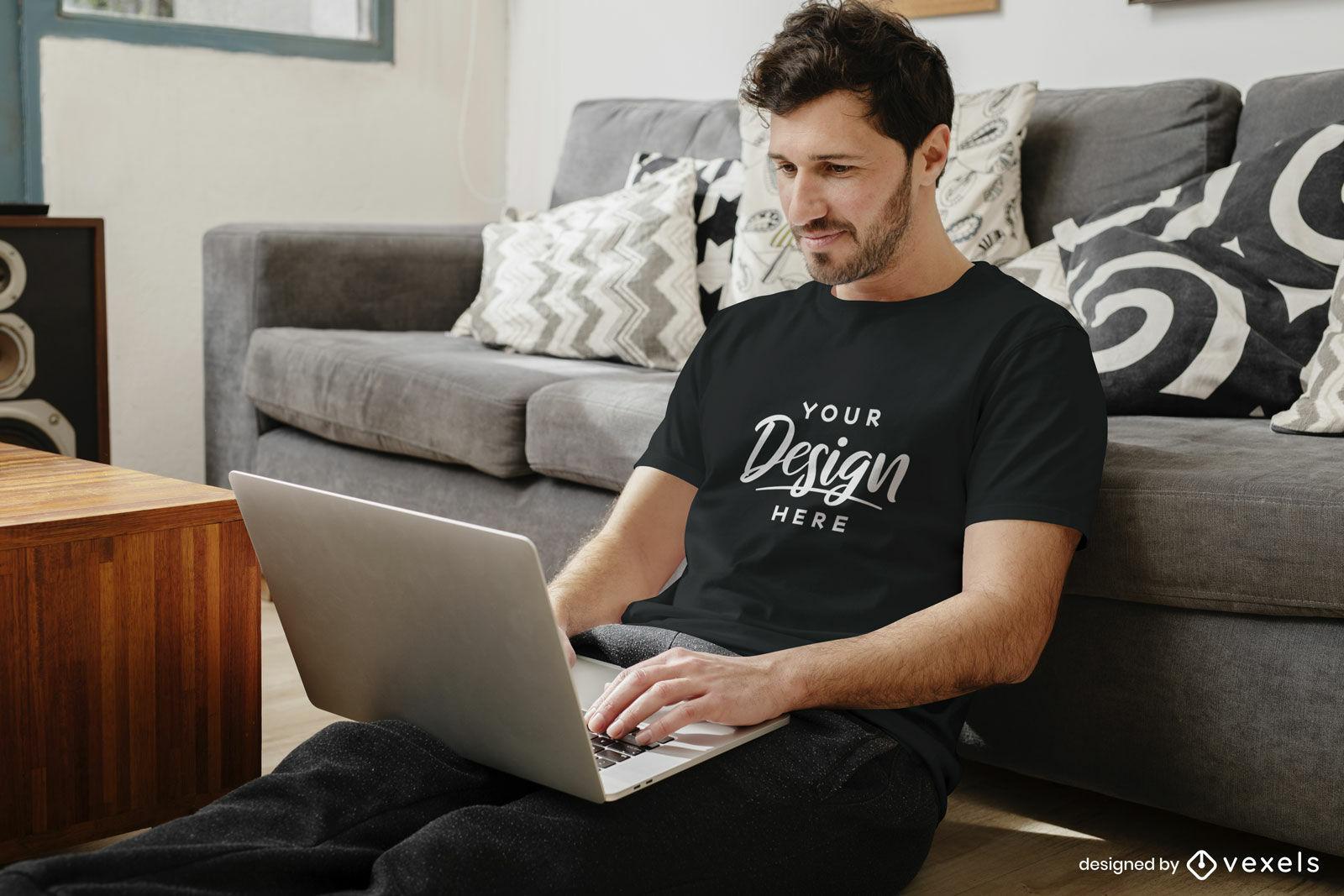 Maquete de camiseta preta homem na sala de estar com laptop