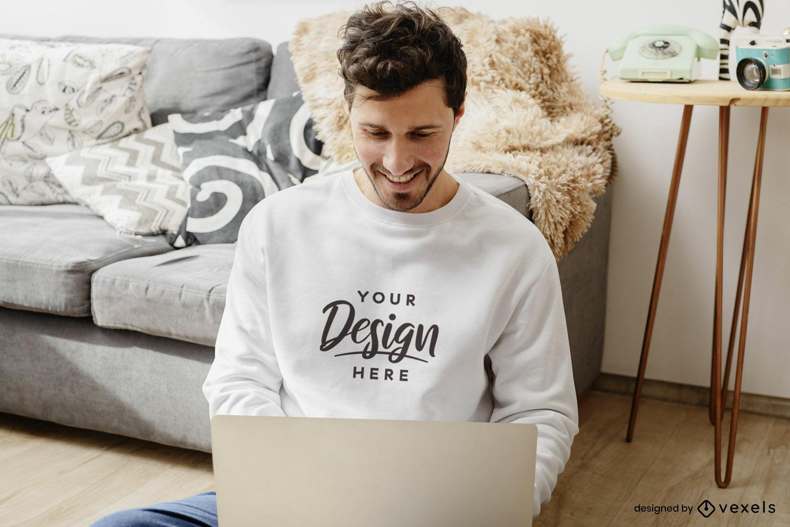 Homem de moletom branco com maquete da sala de estar do laptop