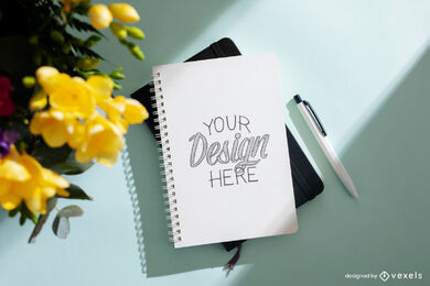 Notebook in surface with flowers mockup