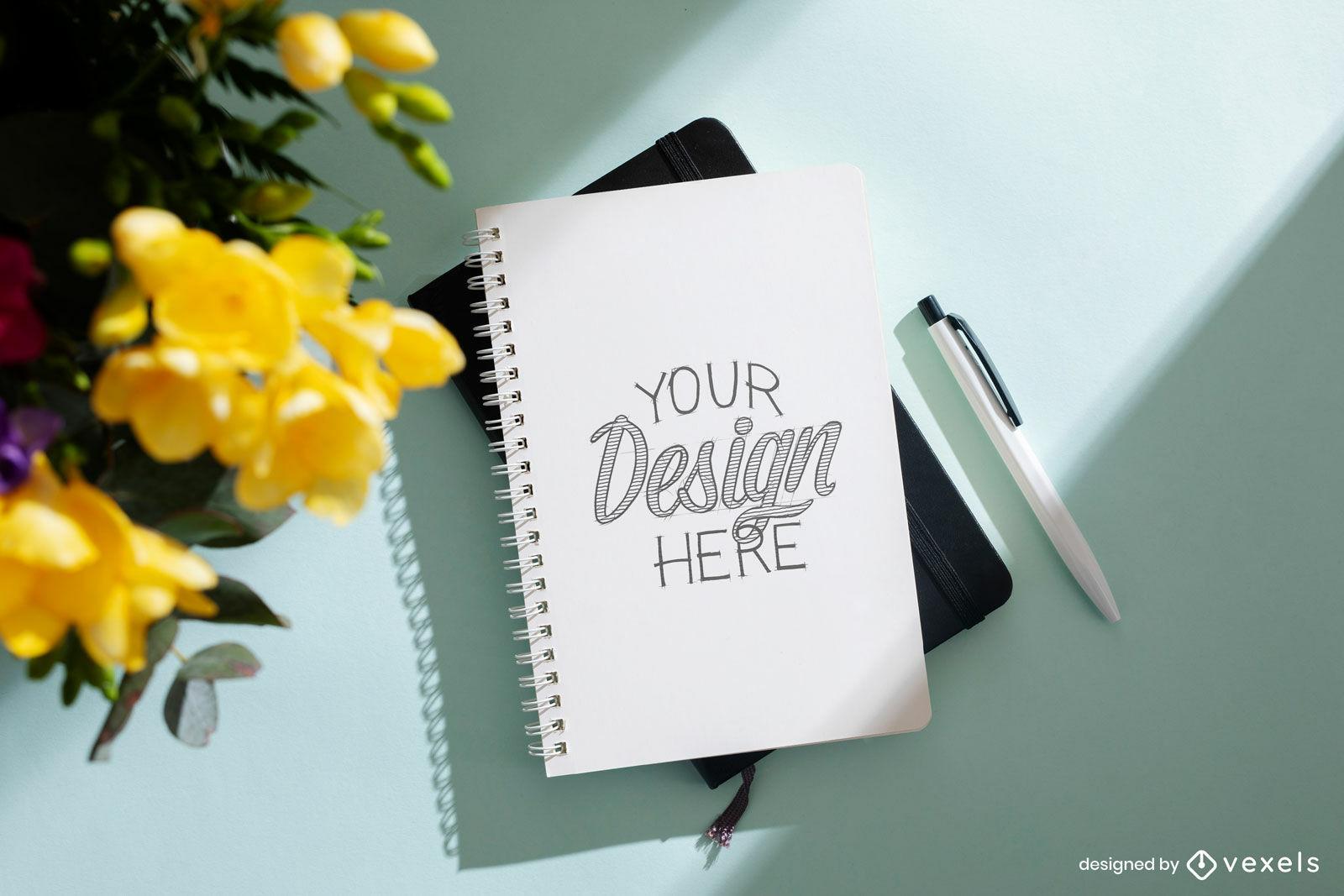 Cuaderno en superficie con maqueta de flores.