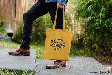 Bolso tote amarillo con maqueta de hombre en jardín