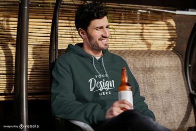 Mann mit Hoodie trinkt Biermodell
