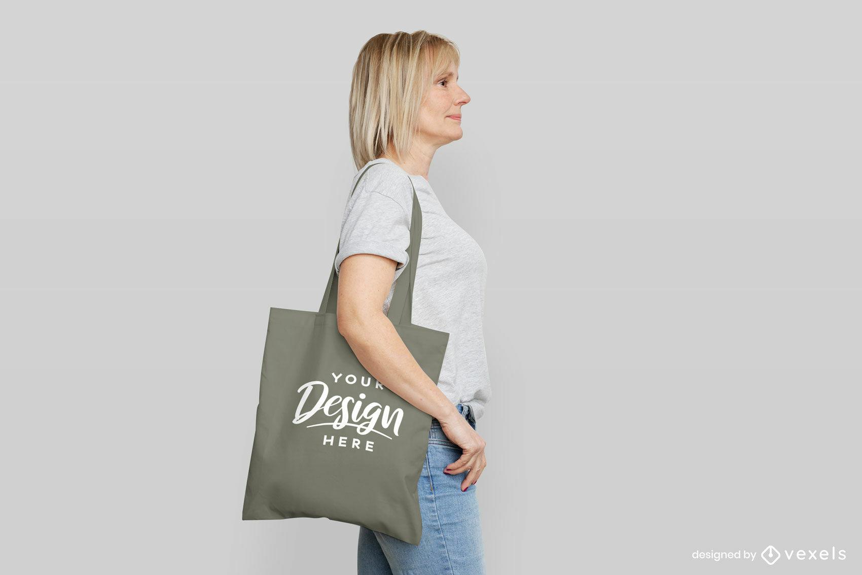 Mujer con maqueta de bolso gris en fondo plano