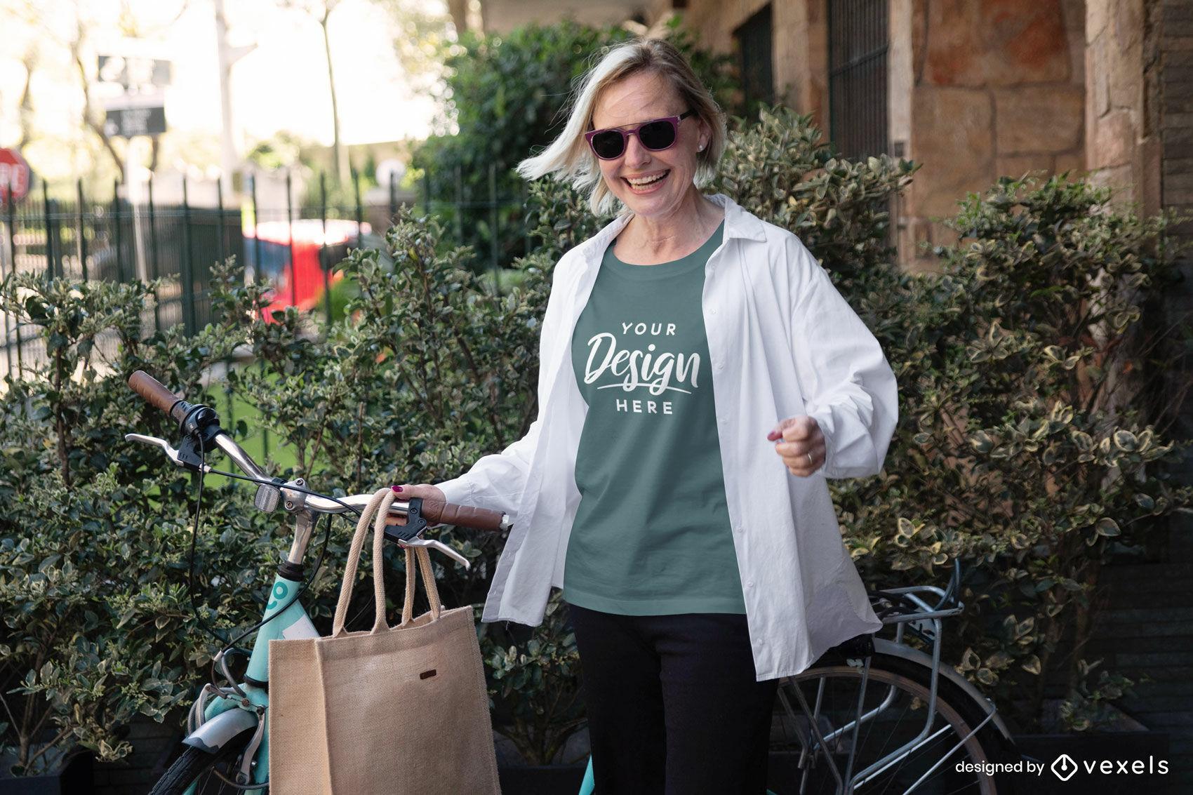 Mulher no jardim com maquete da camiseta verde da bicicleta
