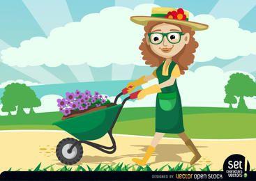 Gärtnerfrauen, die Pflanzen durch Schubkarre tragen