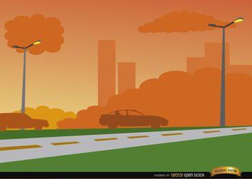 Puesta del sol anaranjada en fondo del camino de ciudad