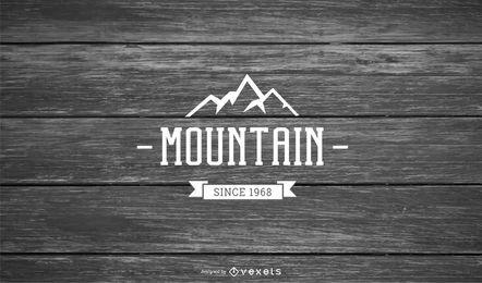 Logo de montaña sobre fondo de madera
